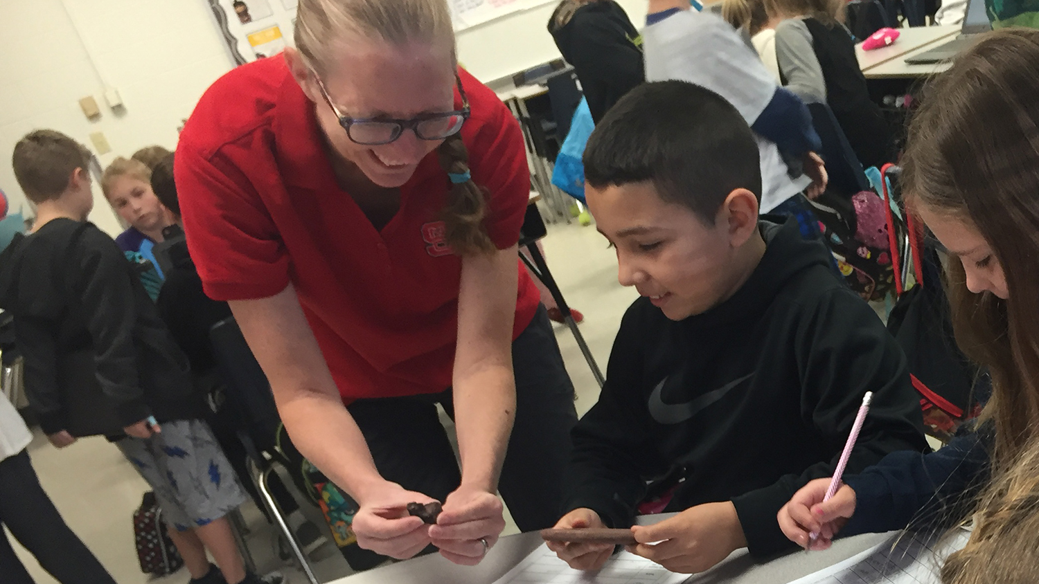 teacher showing students a space rock
