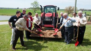 people shoveling dirt from front of a tractor at a ground-breaking event