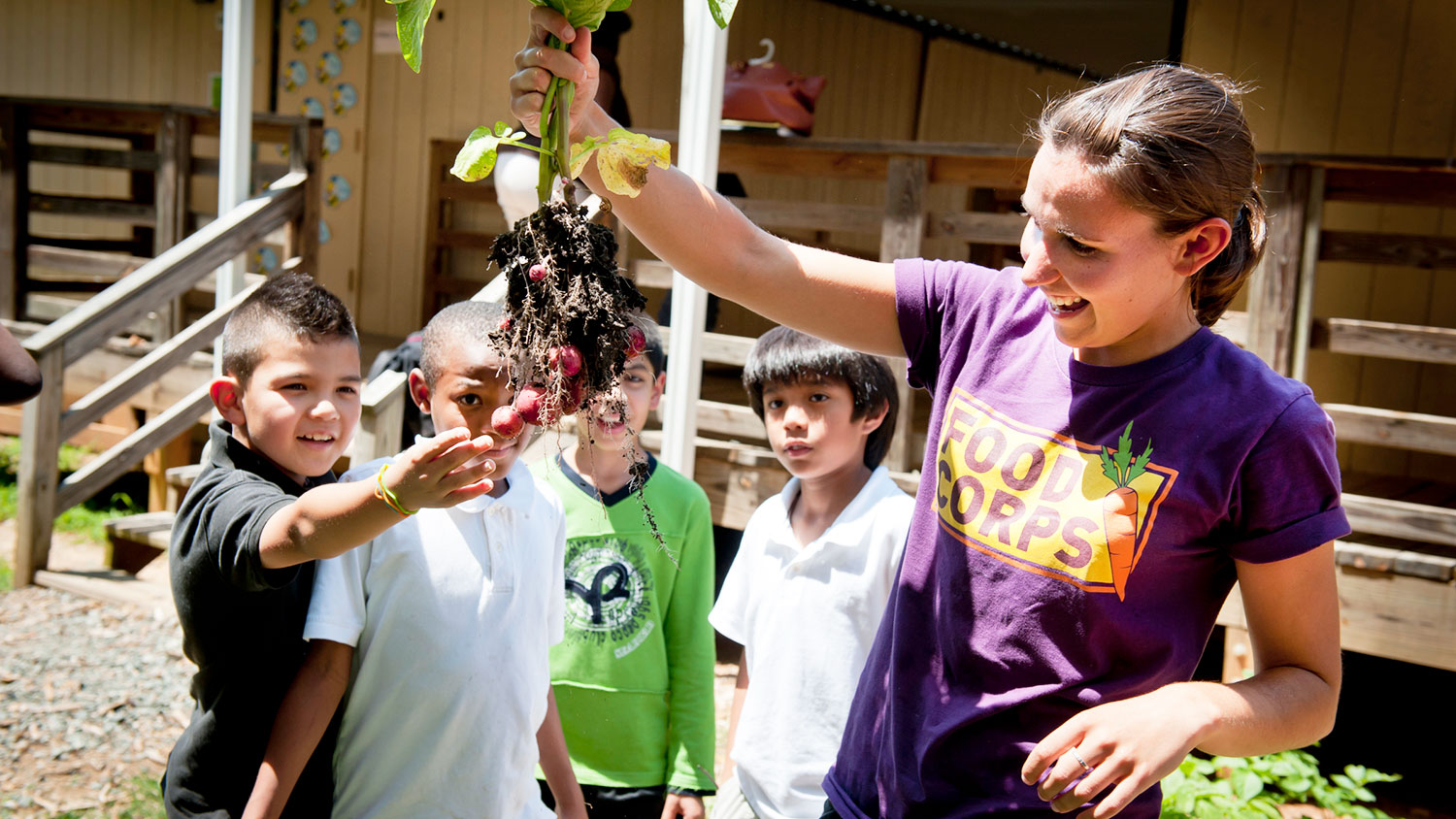 A Food Corps volunteer shows a group of children vegetables just pulled from the ground.