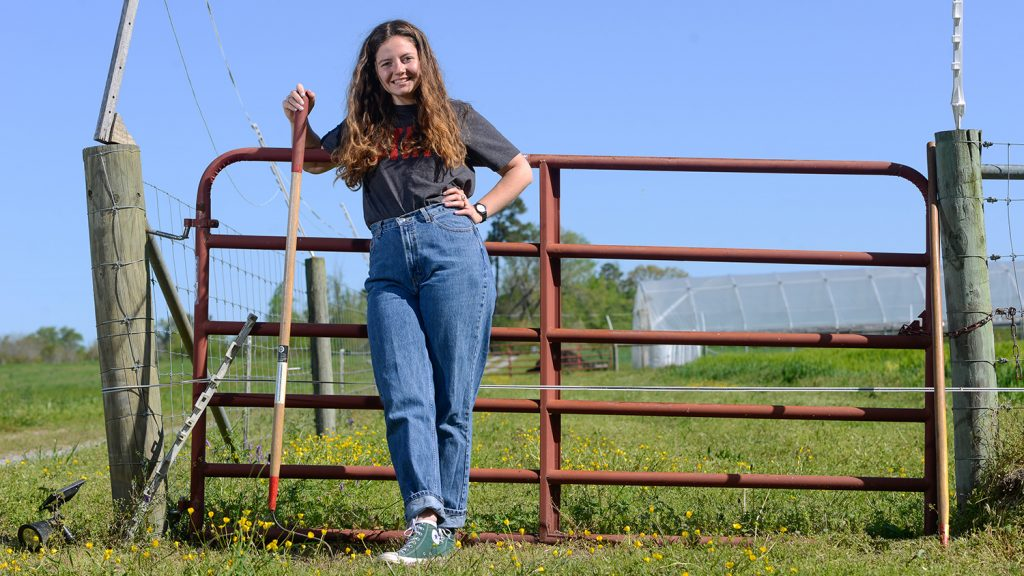 CALS Agroecology student Eliza Hardy stands by a fence