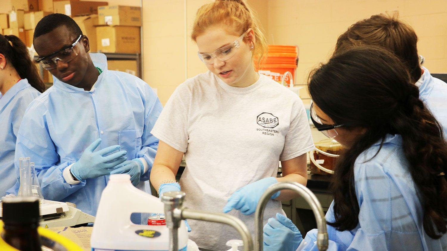 Female student working on an experiment with other students