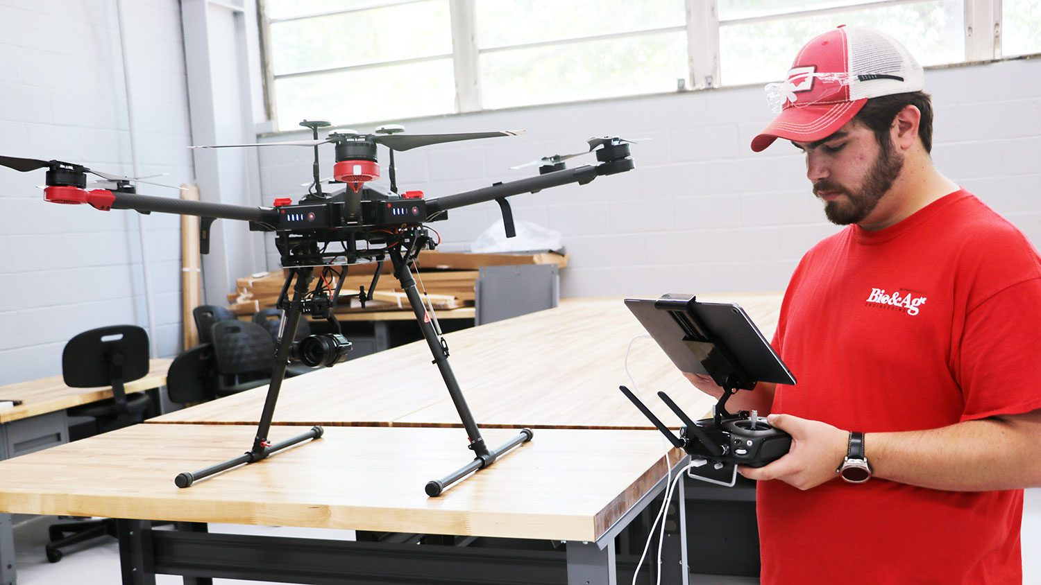 Man looking at the controls for a drone that is sitting on the table next to him.