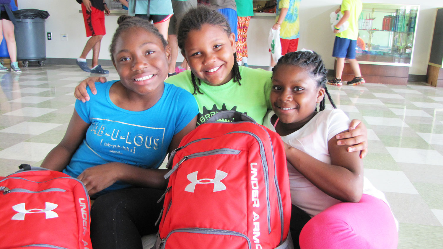 three girls sitting with a backpack
