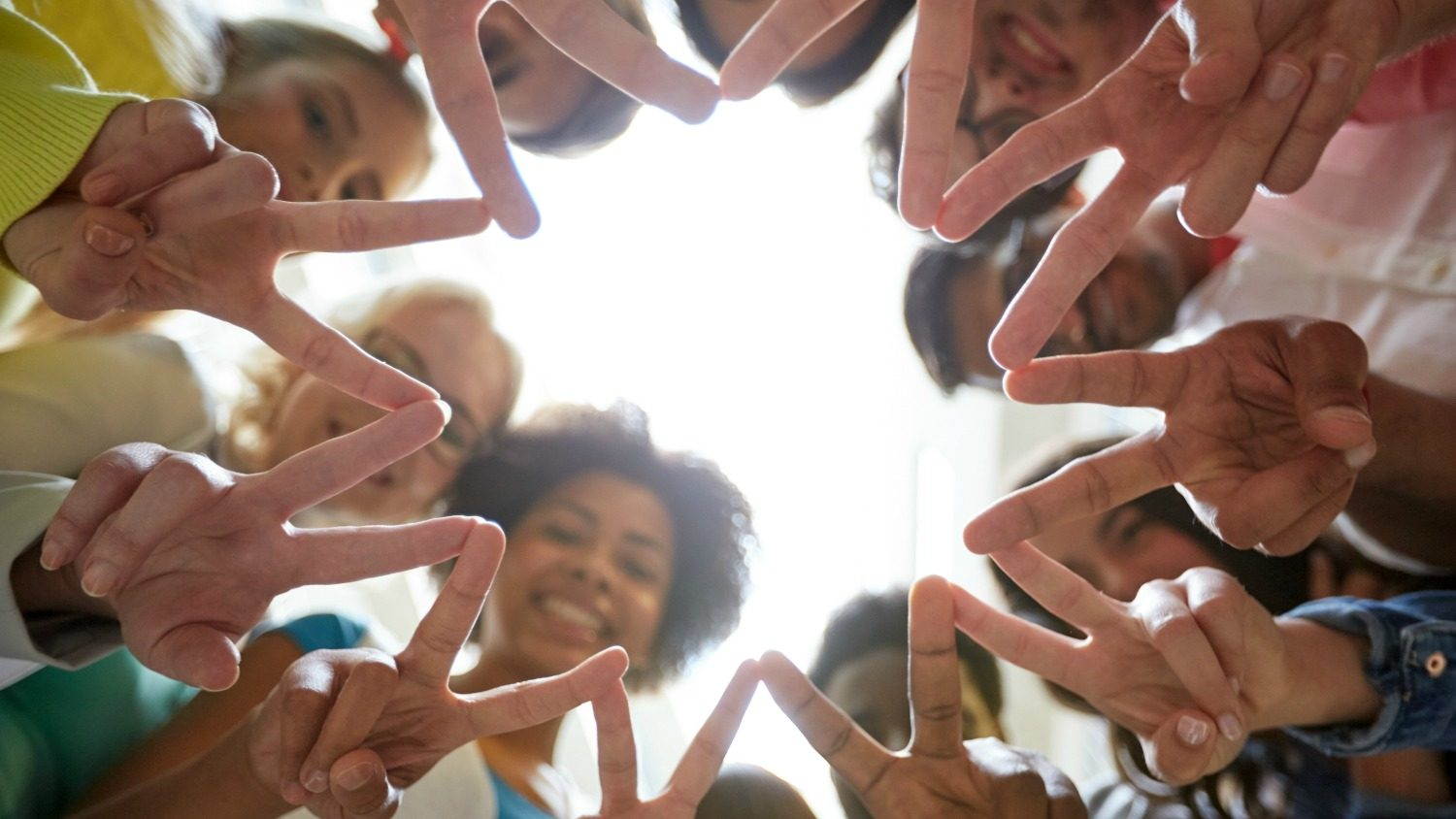 Diverse people in a circle with peace signs.