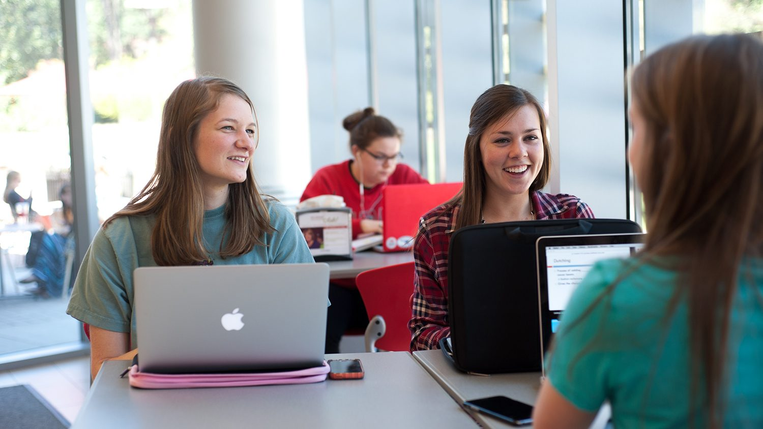 Three female students with laptops laughing in the library.