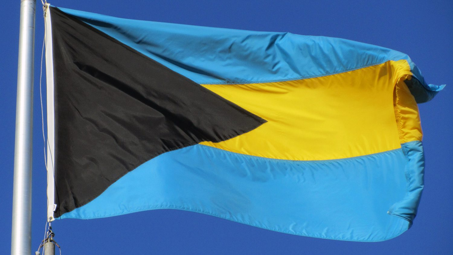 Blue flag with a yellow stripe and black triangle, Bahamas flag