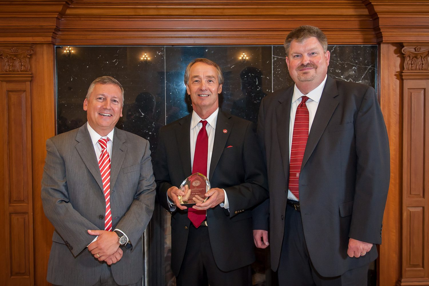Three men standing in suits while the one in the middle is holding an award.