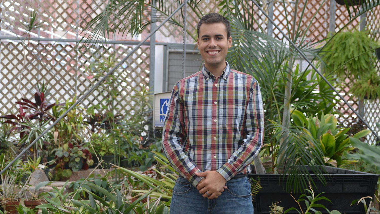 Student in NC State Conservatory (greenhouse)