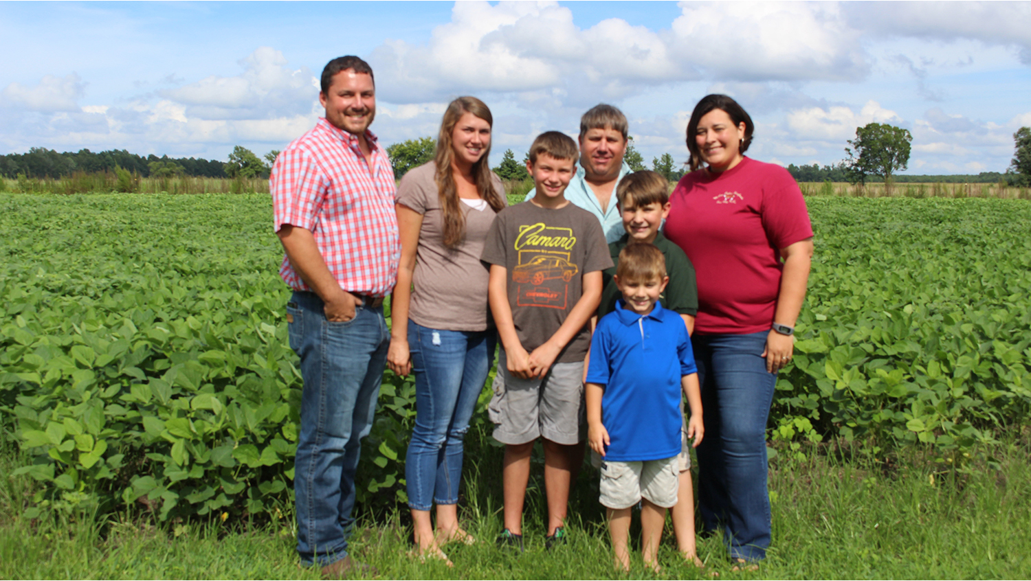 Four adults and three children gathered together near a farm field.