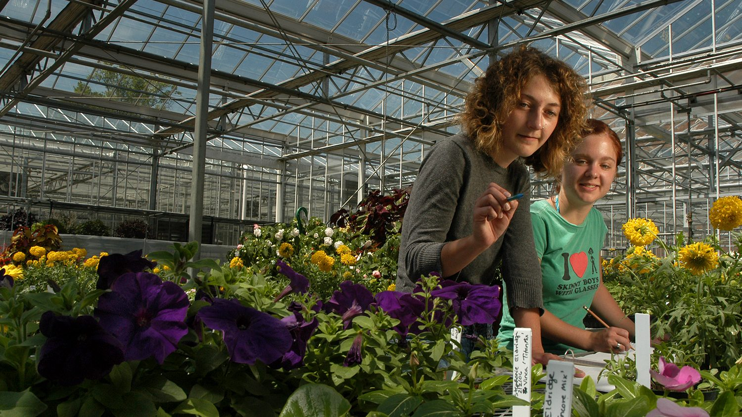 Faculty member with student in greenhouse.