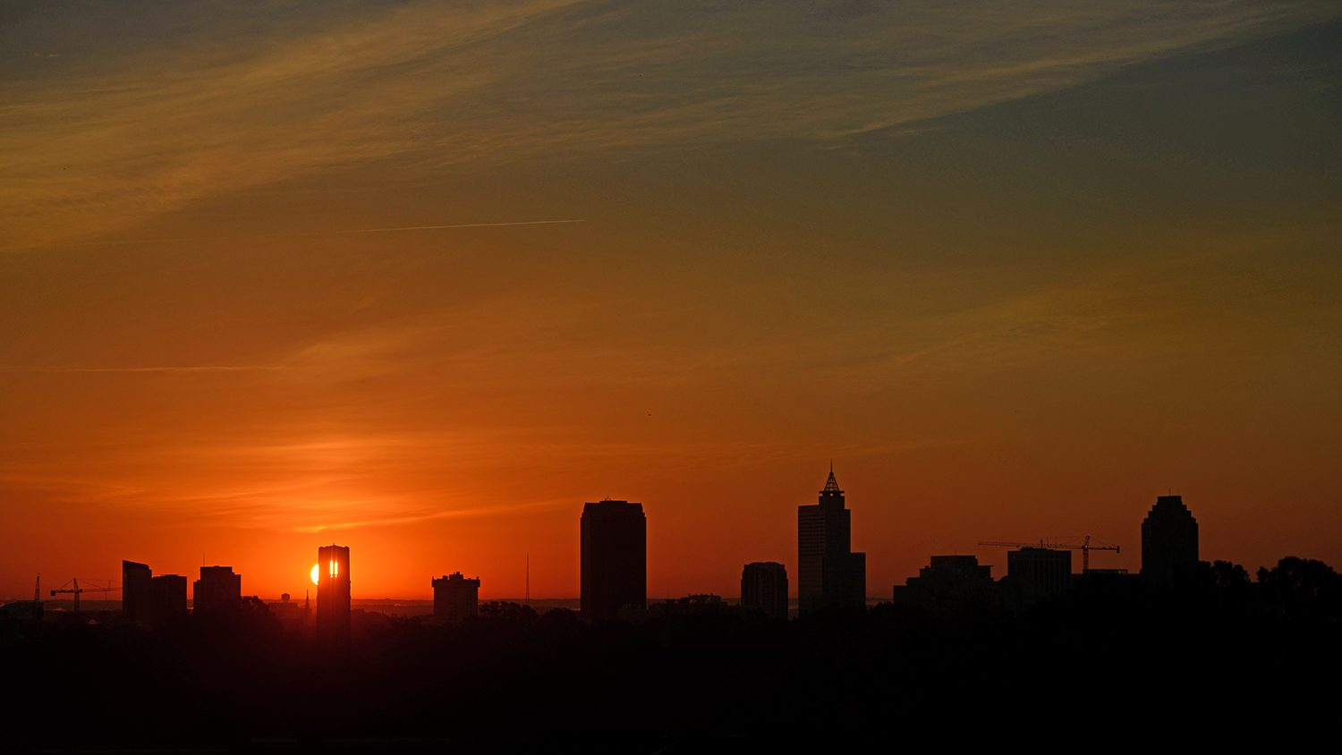Sun rise silhouettes the Raleigh skyline