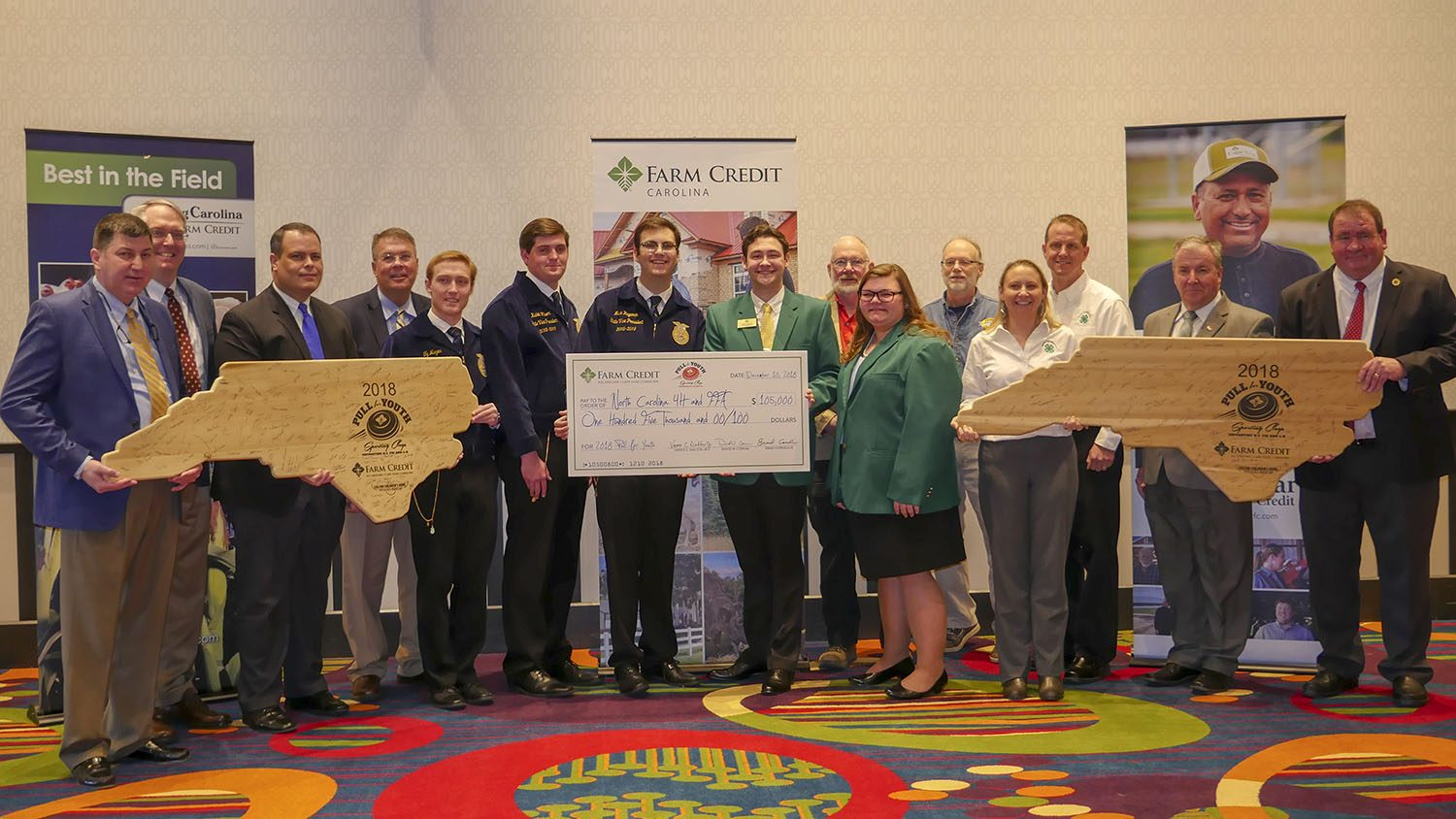 15 people holding a check for $105,000 and two large wooden plaques in the shape of North Carolina