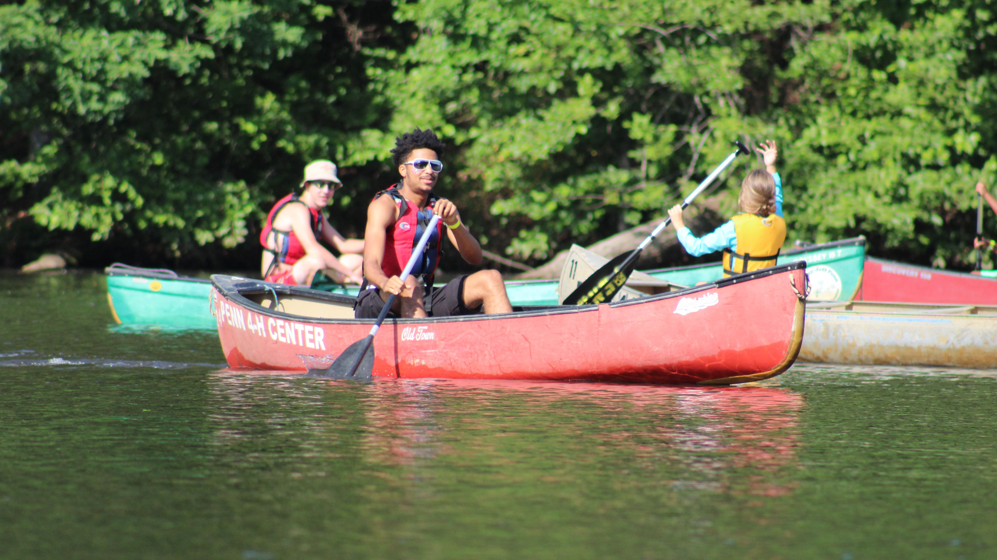 Taqqee paddles in canoe with 4-H campers.