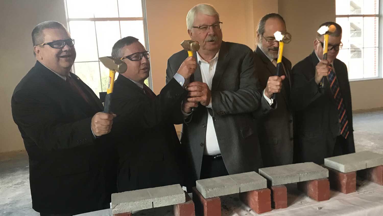 Five men with mallets ceremoniously breaking concrete bricks.