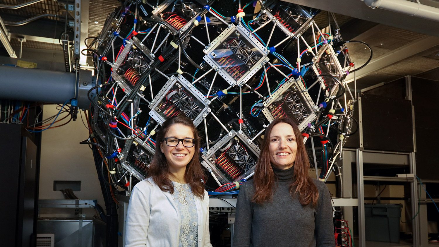 CALS Ph.D. student Gabriela Schroder and CALS professor of biochemistry FLora Meilleur stand in front of a complicated machine at ORNL.