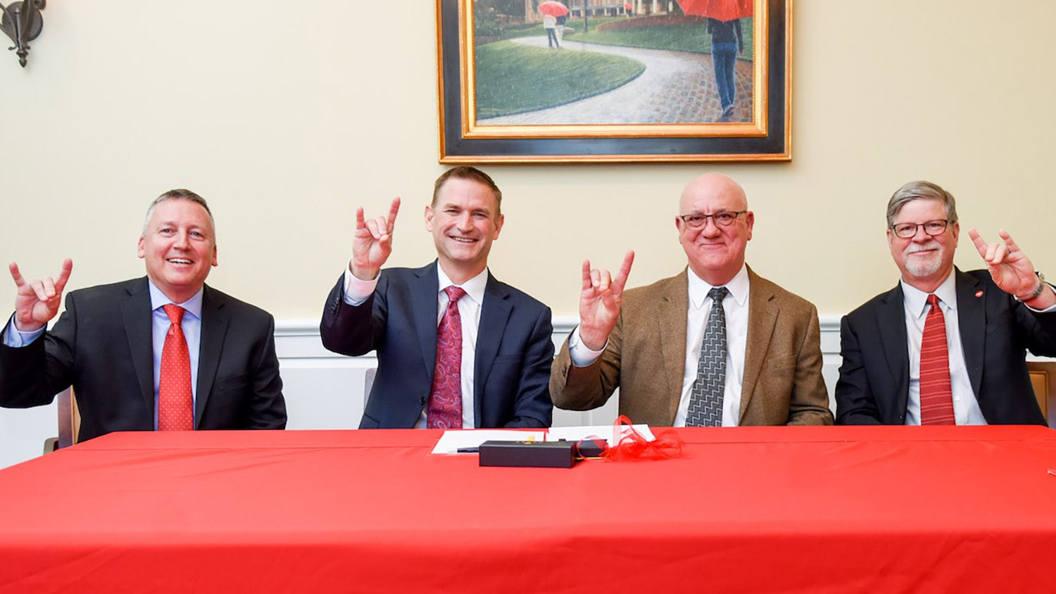 Four men at a red table give the wolf sign.