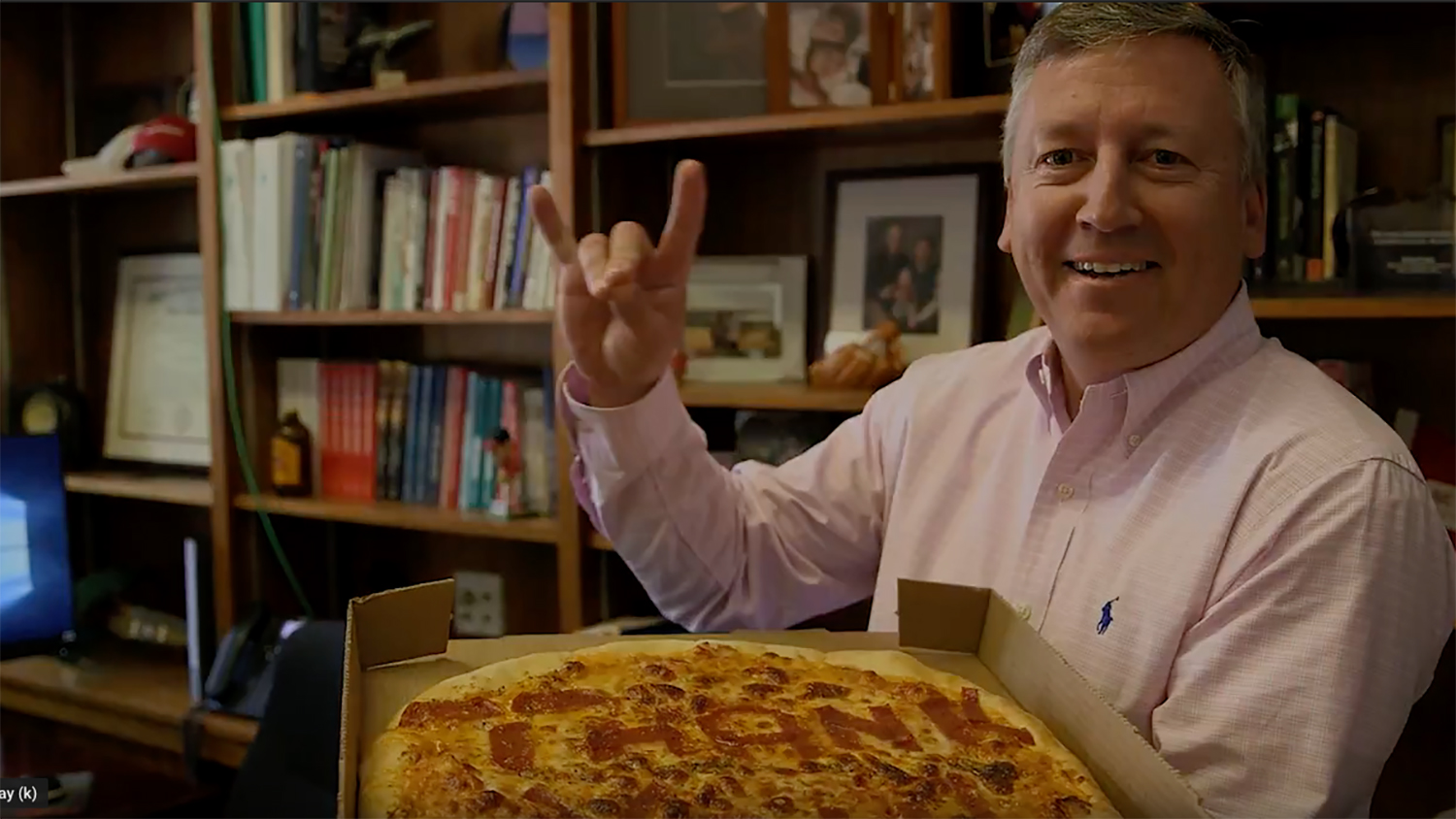 Dean Richard Linton holding a thank-you pizza and giving the Wolfpack sign.