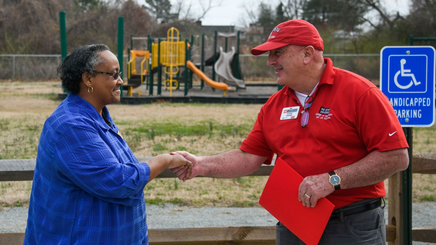 Two people shake hands. Playground equipment behind them.