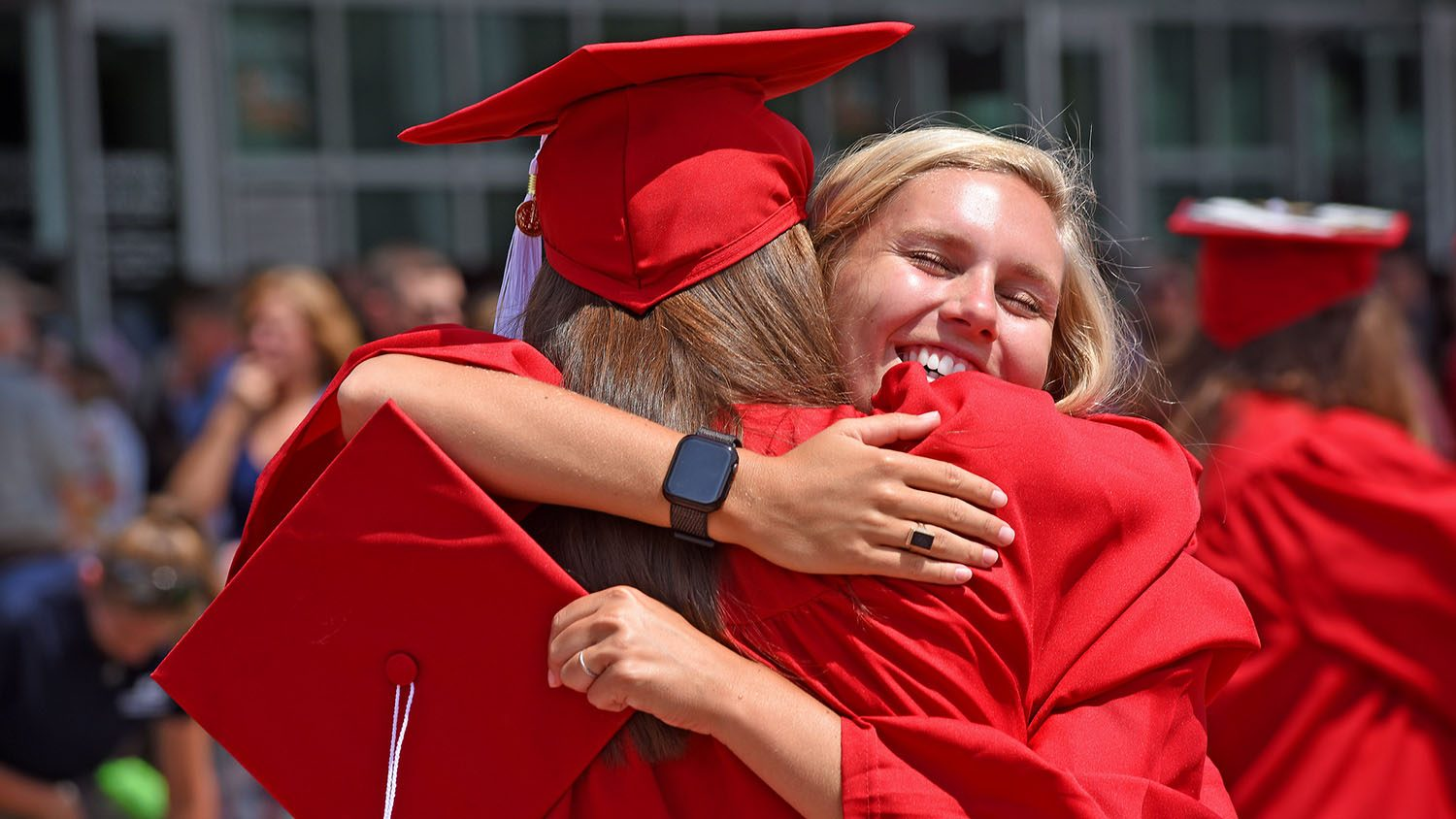 Graduates celebrate their success with a hug.