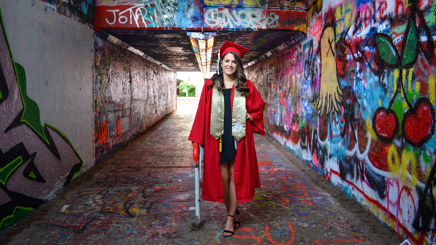 A CALS NC State graduate stands in the Free Expression Tunnel, framed by graffiti.