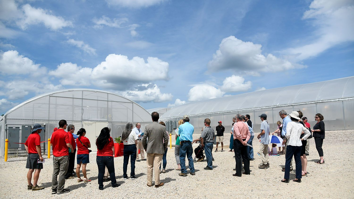 Group of adults gathered outside of greenhouses listening to a speaker