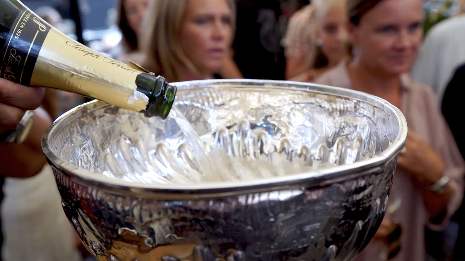 Someone pouring champagne into the Stanley Cup with two women in the background.