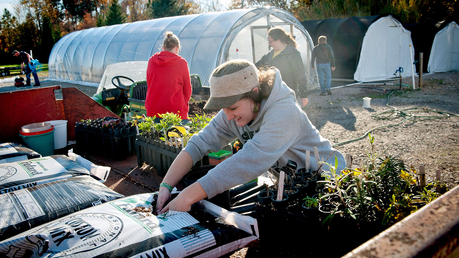 Capped girl digging into a bag of dirt with plants in front of her and greenhouses behind her, haloed by light.