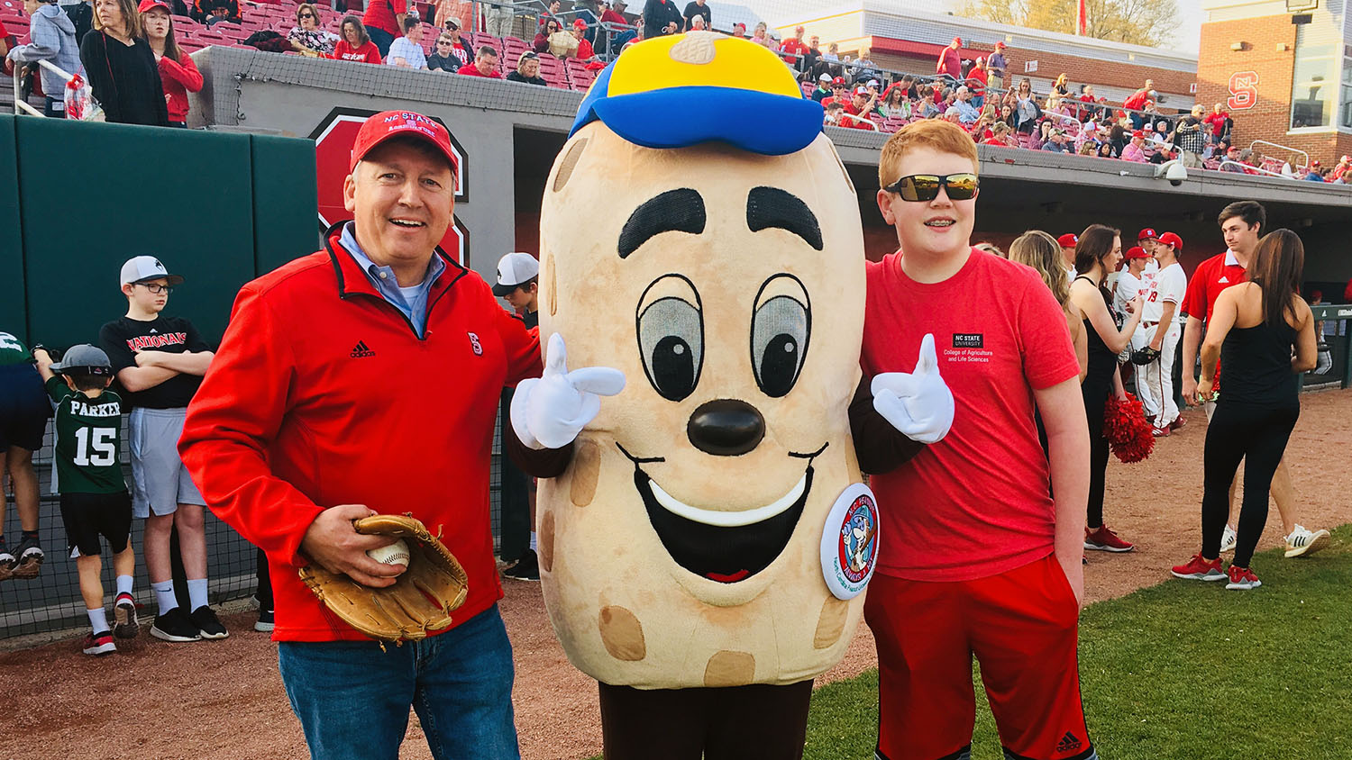 CALS Dean Richard Linton stands with a sports mascot with his son at a baseball game for Father's Day
