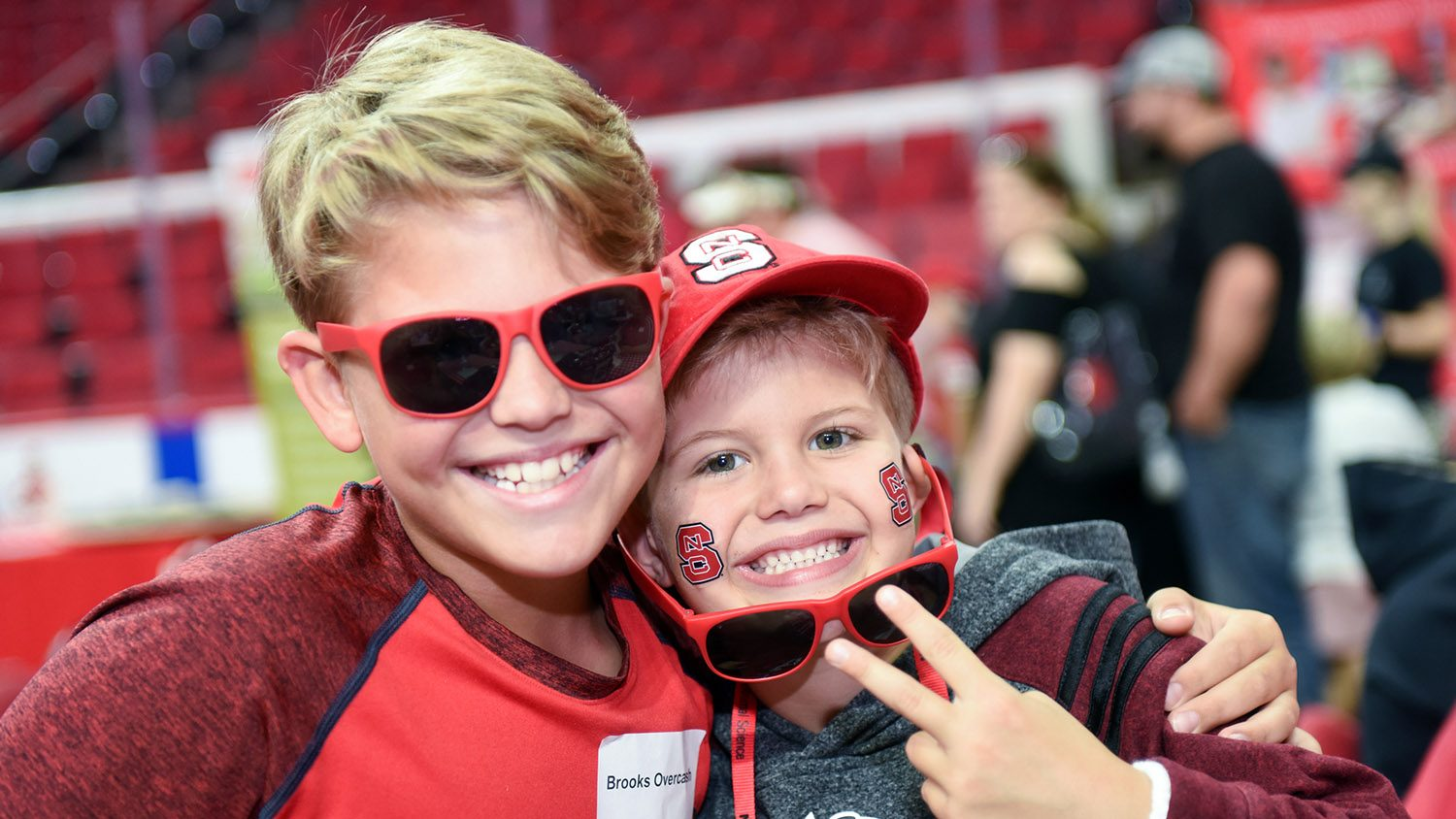 Two young boys, one in red shirt with red sun glasses, the other with a red NC State hat, red sunglasses and State tattoos on cheeks.