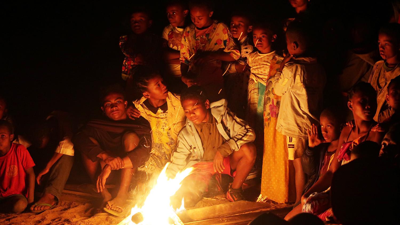 In the dark, children huddling near a fire