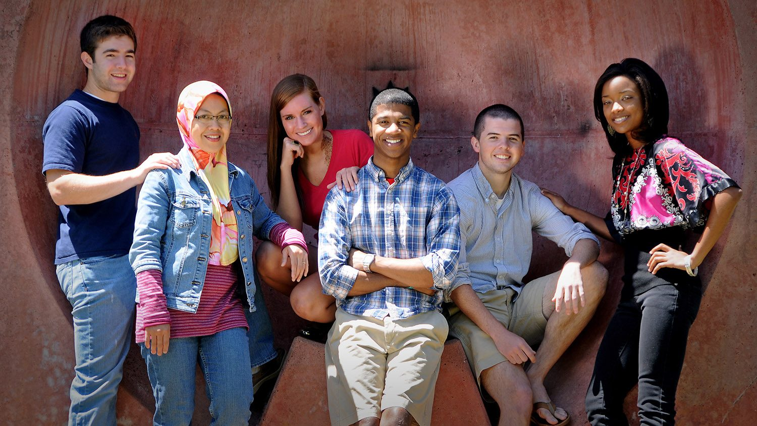 Three female students and three male students pose in the wolf ears in the brickyard.