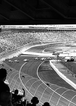 Black and white photo of cars racing with a large crowd.