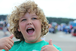 Young white boy with curly blond hair, smiling with mouth wide open and thumbs up.
