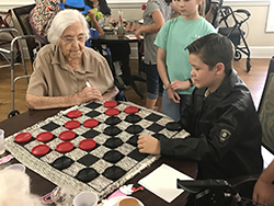 Two young boys, one in a black leather jacket, play checkers with older lady in retirement home.