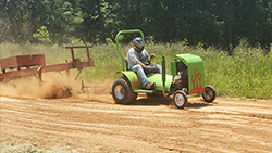 Man with helmet riding a modified lawnmower.