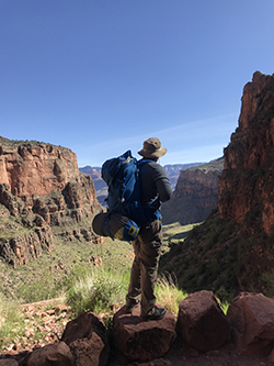 Man with hiking backpack and hat looks out on the landscape. Mountains in background.