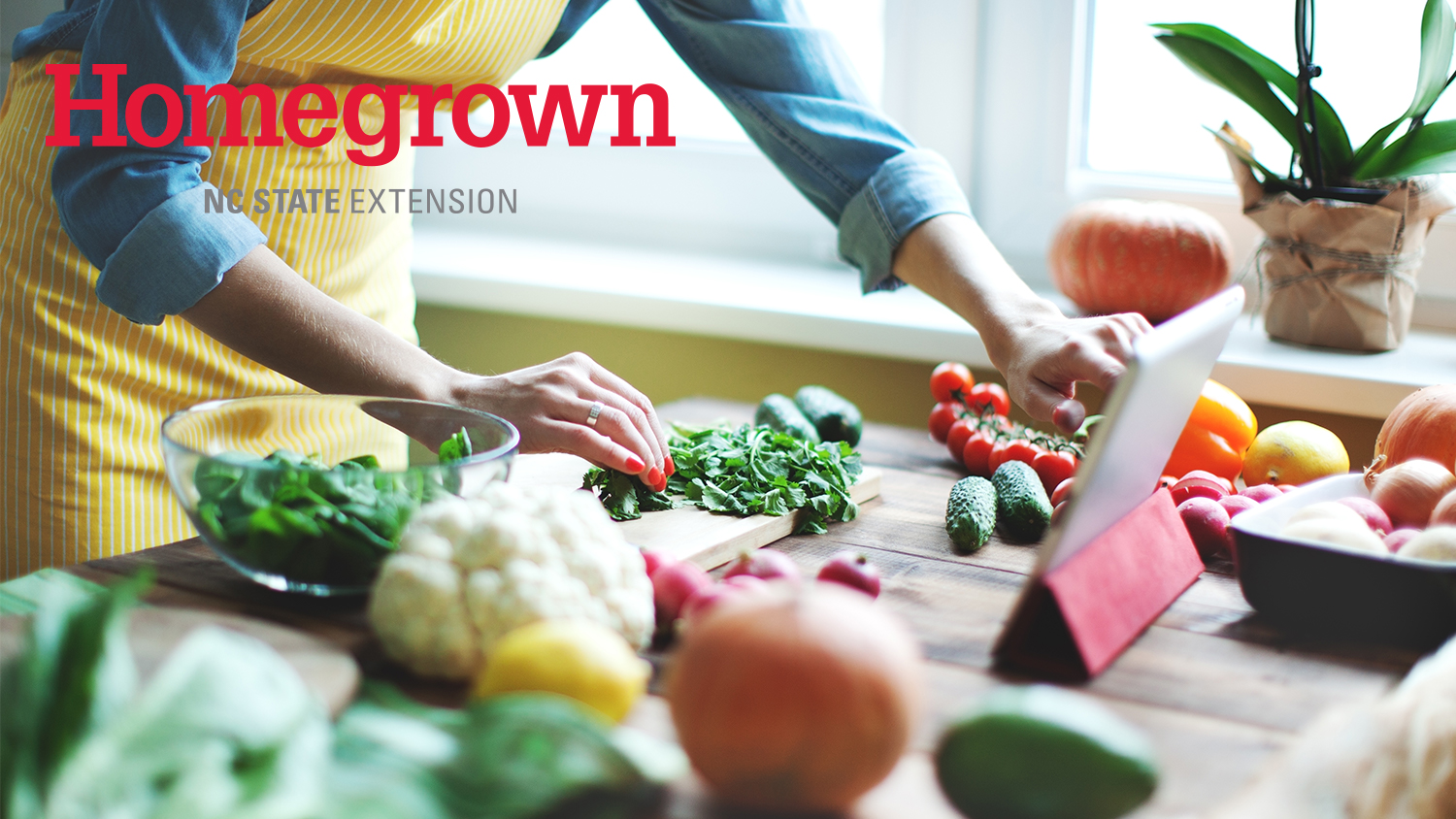 Person leaning over counter looking at tablet with lots of vegetables around.