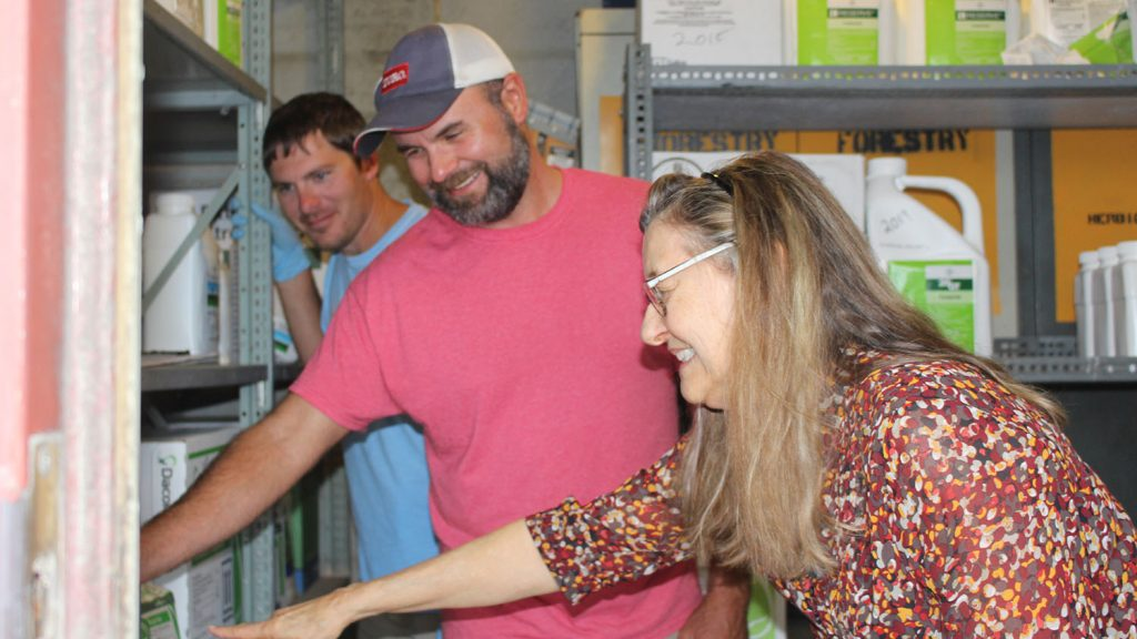 Candy Orr with Marty Parish and Dustin Corbett within a pesticide storage bunker.