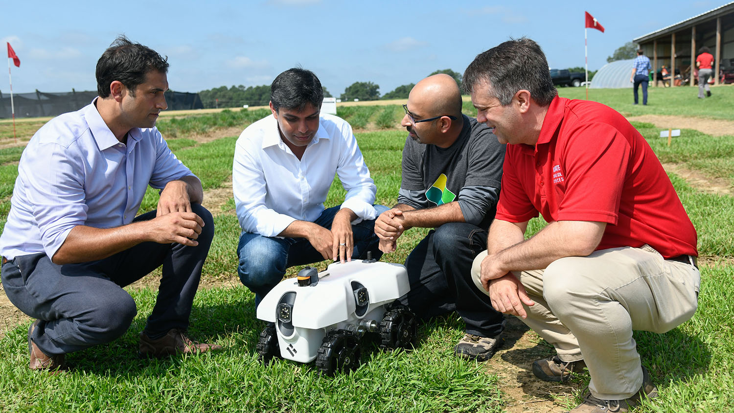 Chris Reberg-Horton and Steven Mirsky, co-leaders of a $10M sustainability grant examine an autonomous ag data collection robot.