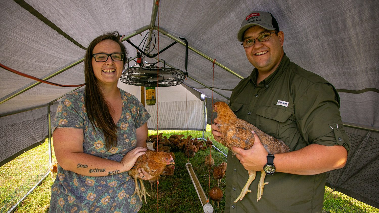 Man and woman holding hens.