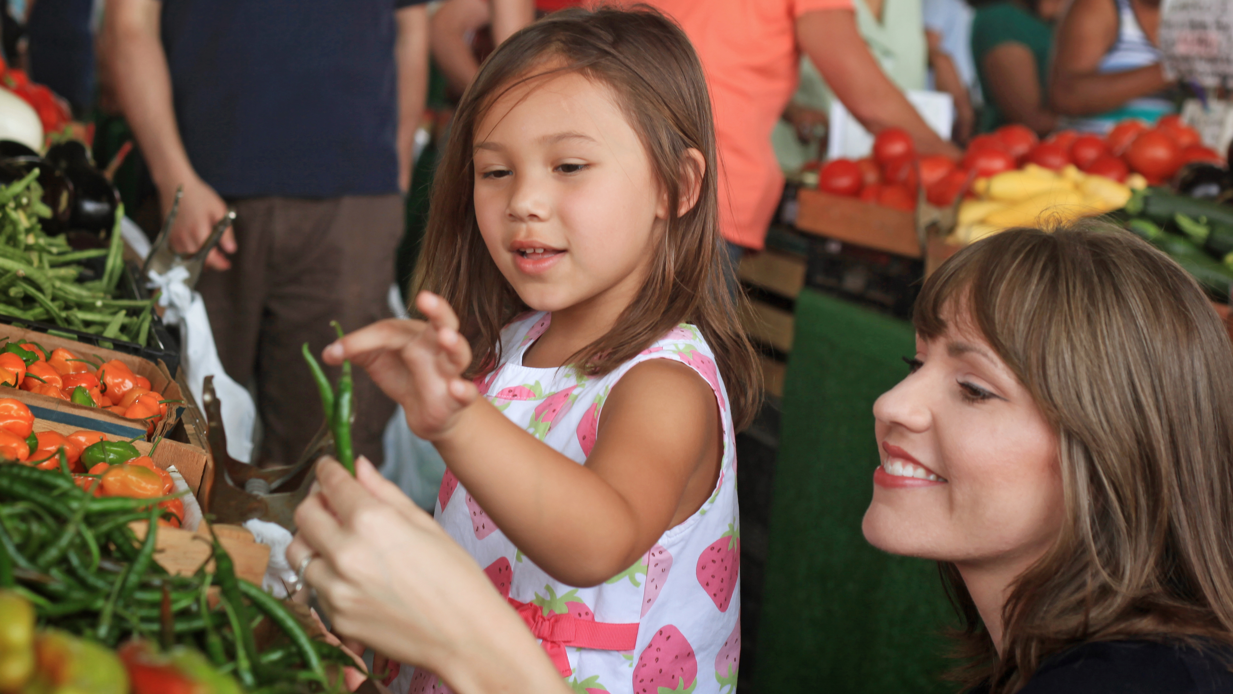 Woman and girl looking at beans at a farmers' market.