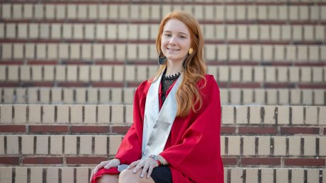 Woman in a graduation robe sitting on brick stairs