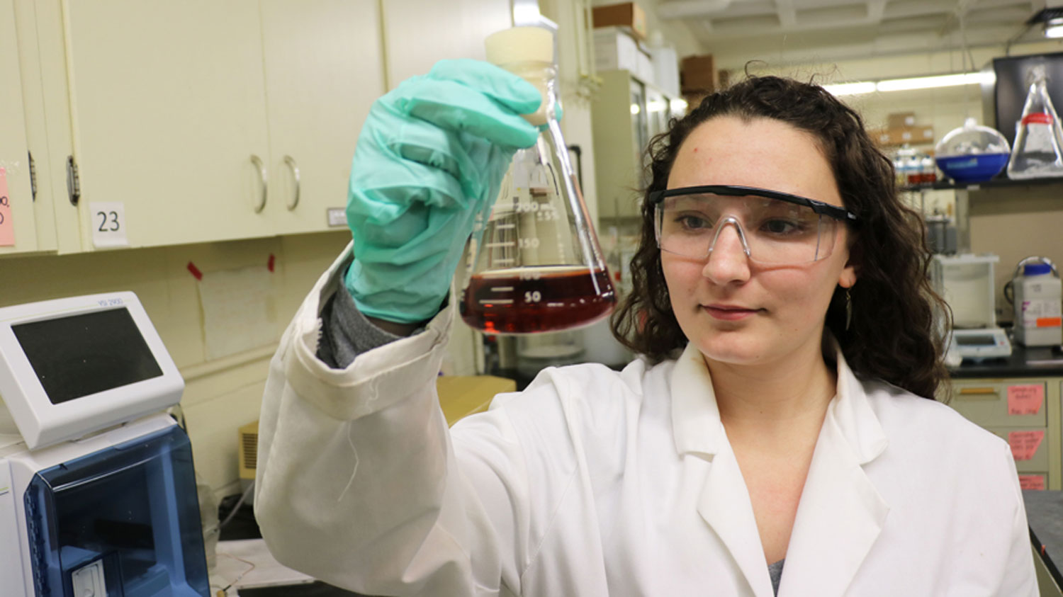 Young woman holding a flask in a lab