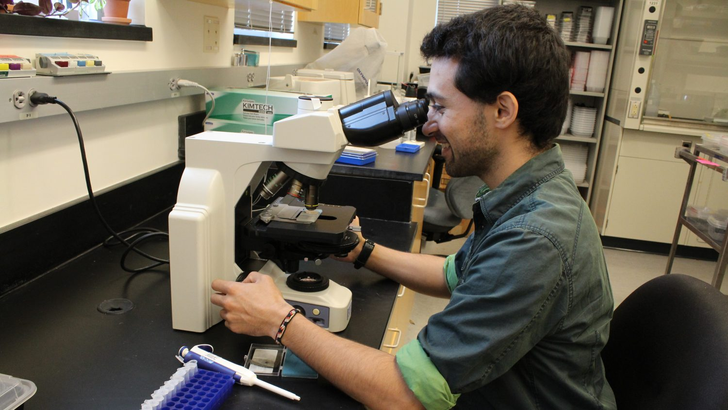 Man looking through a microscope in a lab