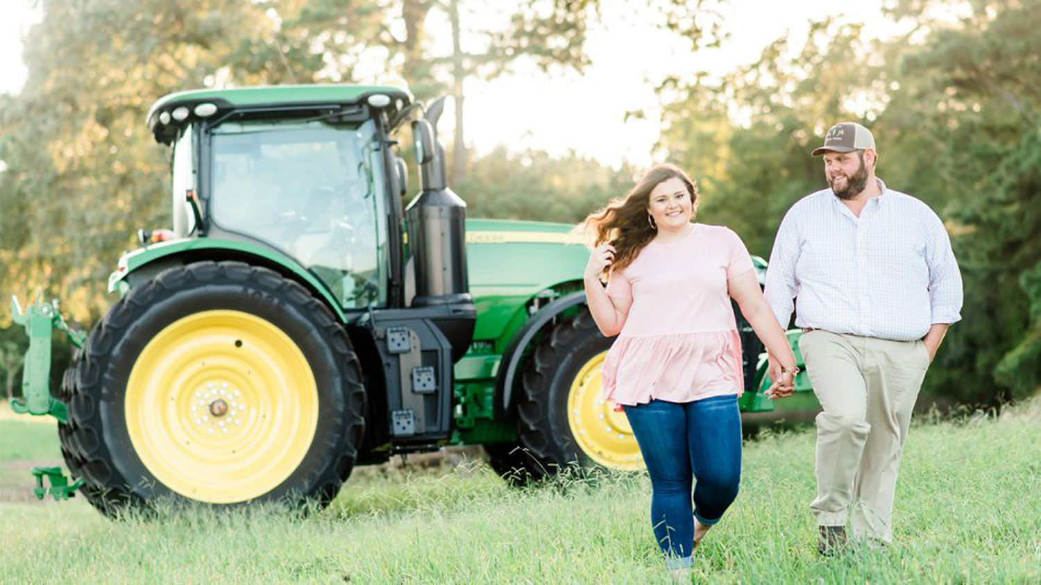 A young woman and man hold hands ina field with a tractor behind them