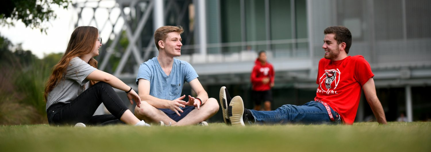 Three students talk while sitting on the lawn at Stafford Commons in front of Talley.
