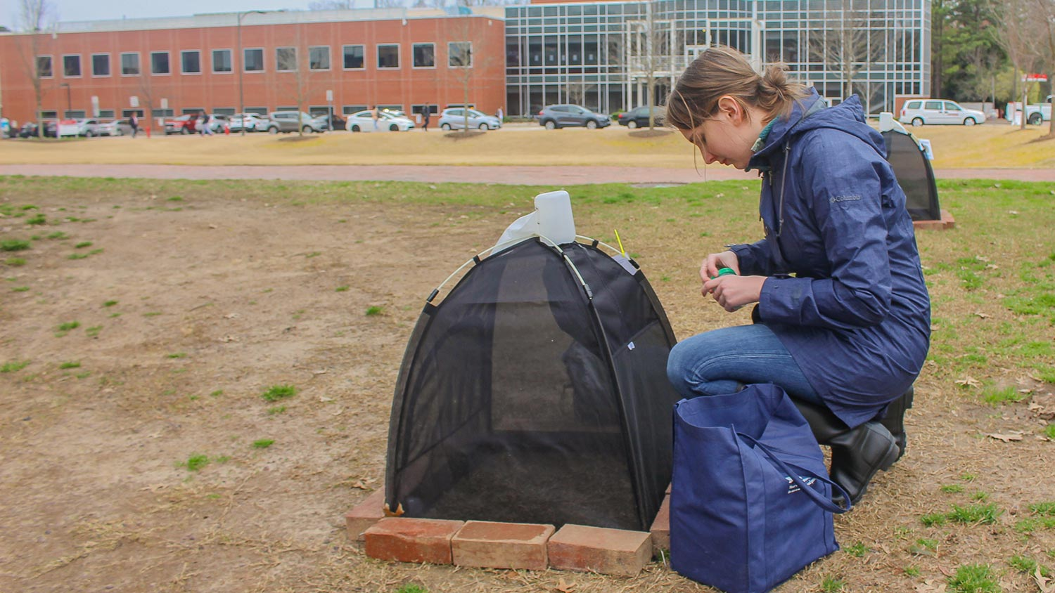 Young woman next to a small tent collecting data for research