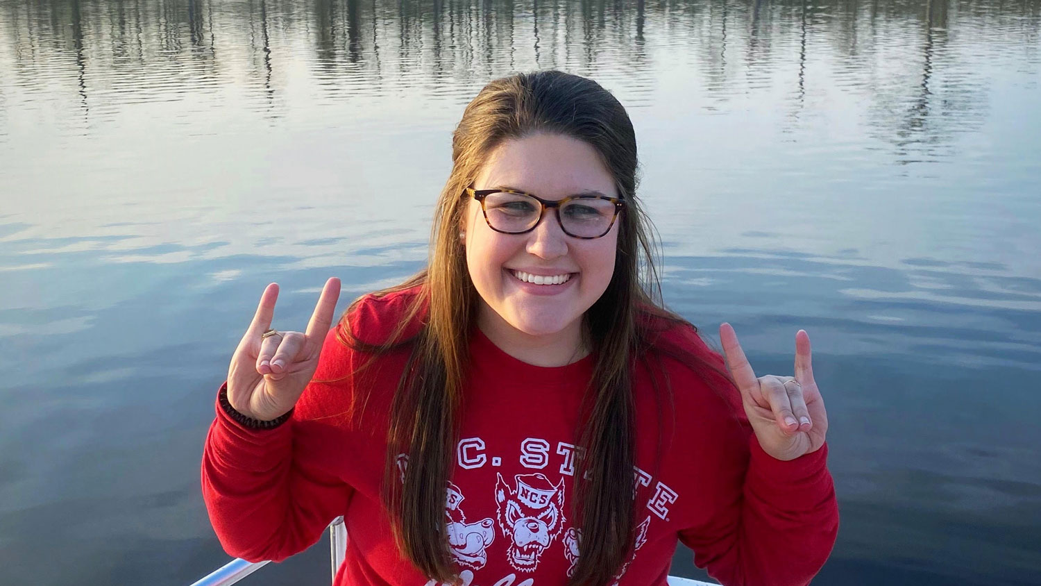 Young woman sitting on a small boat in the middle of water with two wolfpack hands