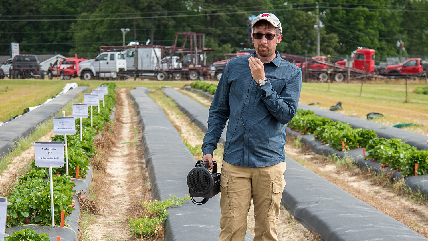 Man in farm field holding speaker and microphone.