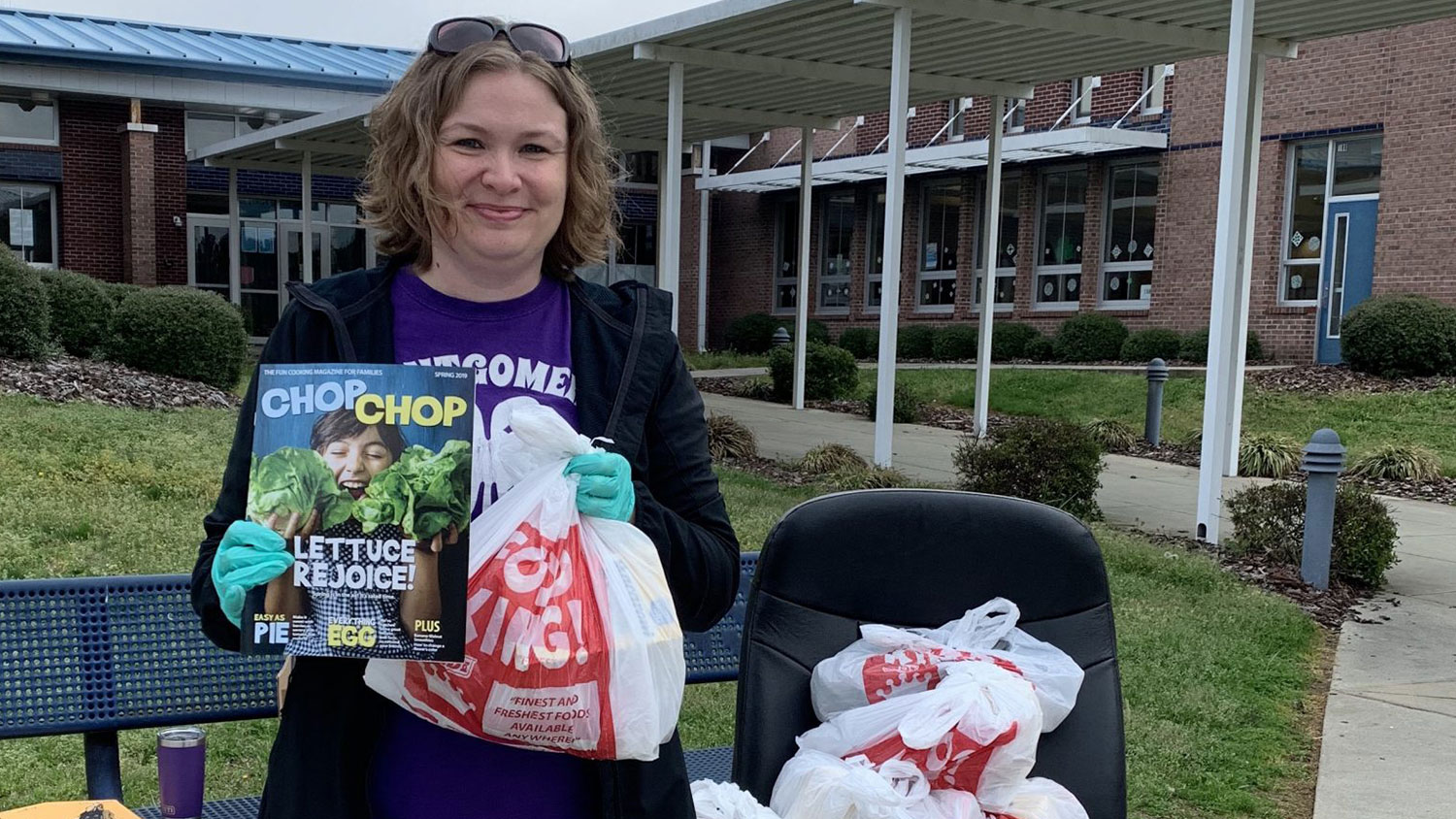 White female outside a school holding a magazine and grocery bags